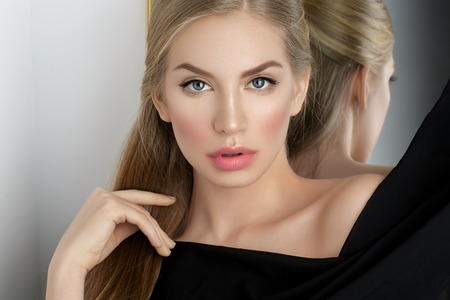 Beautiful young woman with blond hair and makeup covered with piece of black fabric. Copy space. Stock Photo - 58302020