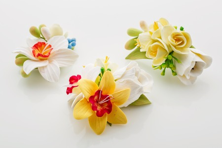 hairclip: Three beautiful handmade art clay spring flower bouquets. Bridal accessory. Boutonniere. Over white background.