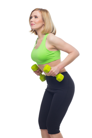 bra top: Beautiful middle aged blond fit woman in green bra top and black pants doing sport exercise with dumbbells. Isolated over white background. Copy space.