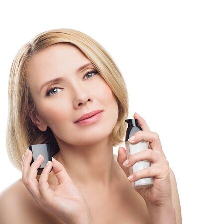Bella donna di mezza età con la pelle liscia e brevi capelli applicando la faccia Siero biondi. colpo di bellezza. Isolato su sfondo bianco. Copia spazio.
