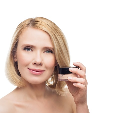 loose skin: Beautiful middle aged woman with smooth skin and short blond hair with loose powder. Beauty shot. Isolated over white background. Copy space.