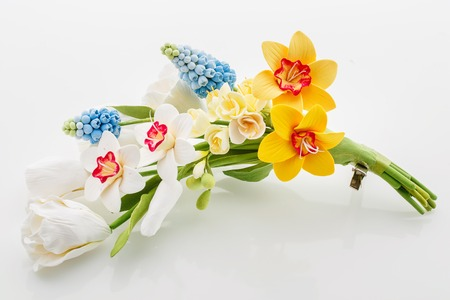 bridal hair: Beautiful handmade art clay spring flower bouquet. Bridal hair accessory. Over white background.