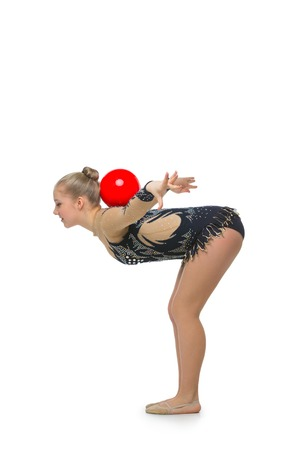 costume ball: Gymnast girl in beautiful costume making jumping exercise with red ball. Isolated over white background. Copy space.