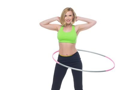 bra top: Beautiful middle aged blond fit woman in green bra top and black pants doing sport exercise with ring hoop. Isolated over white background. Copy space. Stock Photo