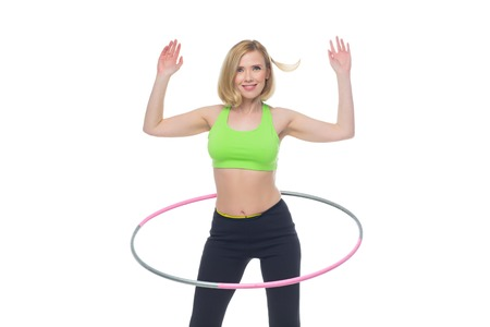 bra top: Beautiful middle aged blond fit woman in green bra top and black pants doing sport exercise with hula hoop. Isolated over white background. Copy space.