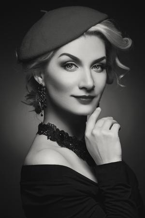film noir: Beautiful lady in beret. Beauty portrait. Film noir retro style. Over black background. Monochrome.