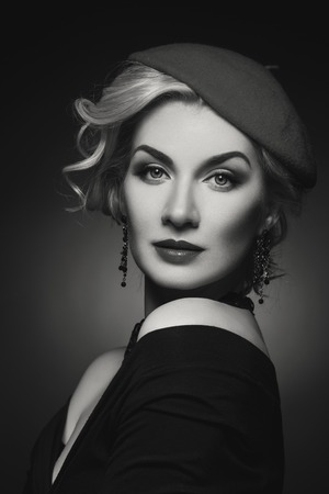 Beautiful lady in beret Over black background. Monochrome.