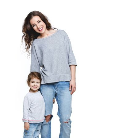 Beautiful young woman with little girl. Mother and daughter isolated over white background. Copy space. Stock Photo