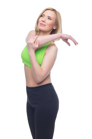 bra top: Beautiful middle aged blond fit woman in green bra top and black pants doing sport exercise. Isolated over white background. Copy space. Stock Photo