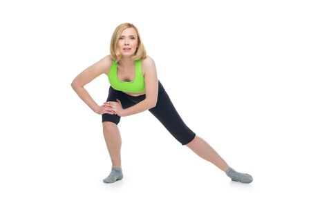 Beautiful middle aged blond fit woman in green bra top and black pants doing sport exercise. Isolated over white background. Copy space. Stock Photo