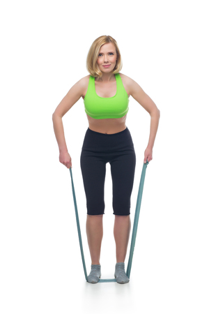 Beautiful middle aged blond fit woman in green bra top and black pants doing sport exercise with rubber. Isolated over white background. Copy space. Stock Photo
