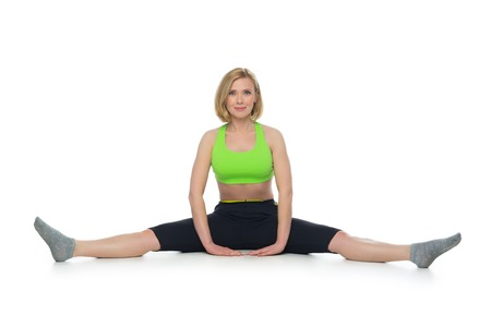 bra top: Beautiful middle aged blond fit woman in green bra top and black pants doing sport exercise. Isolated over white background.