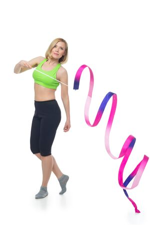 bra top: Beautiful middle aged blond fit woman in green bra top and black pants doing sport exercise with gymnastic ribbon. Isolated over white background.