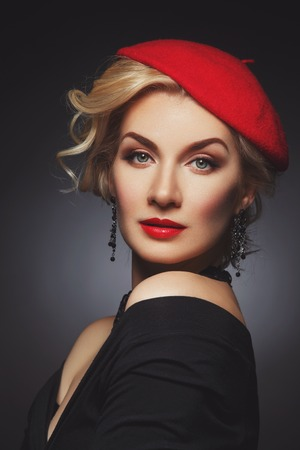 Beautiful lady in red beret. Over black background.