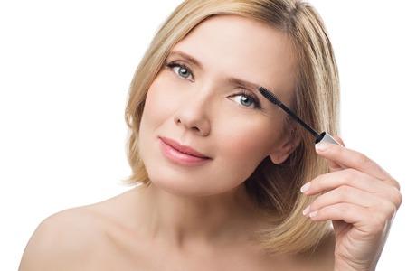 滑らかな肌と短いブロンドの髪を適用する美しい中年の女性は眉毛にゲルを修正します。白い背景に分離されました。