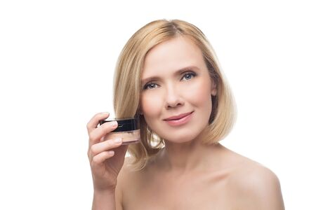 loose skin: Beautiful middle aged woman with smooth skin and short blond hair with loose powder. Isolated over white background. Stock Photo
