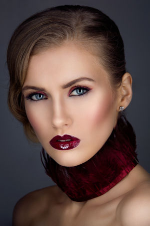 beauty shot: Beautiful girl with red feather collar and bright makeup. Closeup beauty shot. Copy space. Stock Photo