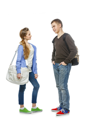 school teens: Beautiful teenage girl and boy in casual clothes with school bags standing over white background. Talking students. Isolated. Copy space.