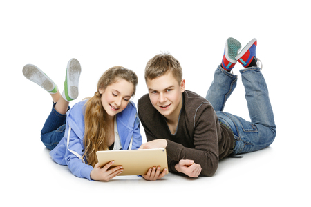 computer isolated: Beautiful teenage girl and boy in casual clothes looking at tablet computer. Students lying over white background. Isolated. Copy space.