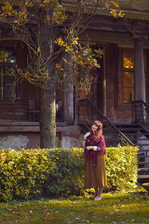 ambient light: Beautiful young woman in long skirt and wool scarf standing near old house. Early fall. Outside shot. Ambient light.