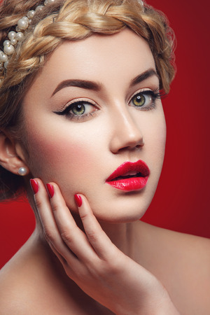 full red: Beautiful young woman with full red lips and braid hairstyle touching face. Beauty shot over red background. Stock Photo