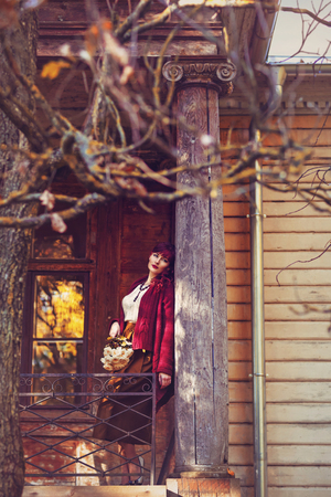 ambient light: Beautiful young woman in long skirt and wool red scarf standing on old house balcony. Early fall. Outside shot. Ambient light.