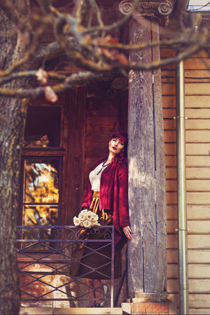 ambient light: Beautiful young woman with flowers in long skirt and wool red scarf standing on old house balcony. Early fall. Outside shot. Ambient light.