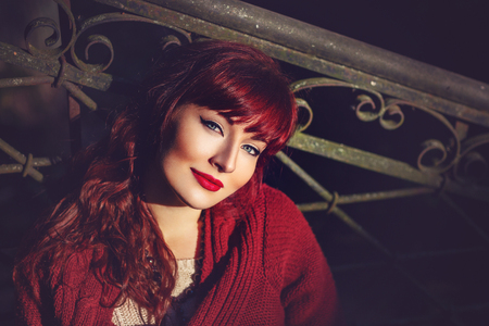 ambient light: Beautiful young woman in wool red scarf sitting on old house stairs. Early fall. Outside shot. Ambient light. Closeup portrait. Copy space. Stock Photo