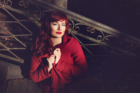 ambient: Beautiful young woman in wool red scarf sitting on old house stairs. Early fall. Outside shot. Ambient light. Closeup portrait. Copy space. Stock Photo