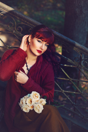 ambient light: Beautiful young woman in long skirt and wool red scarf sitting on old house stairs holding flowers. Early fall. Outside shot. Ambient light. Copy space.