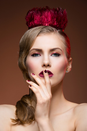provocative woman: Beautiful girl with red feather crown and bright makeup. Closeup beauty shot. Over dark background.