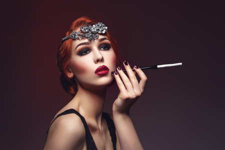 full red: Beautiful young woman with smoky eyes and full red lips holding cigarette holder. Massive crystal hair accessory on head. Retro styling. Studio beauty shot. Copy space.