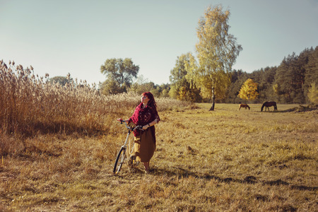long skirt: Beautiful young woman in long skirt and wool scarf riding retro style bicycle in field. Outside shot. Autumn season. Copy space.