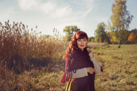 long skirt: Beautiful young woman in long skirt and red wool scarf standing outdoors in countryside. Outdoor shot. Natural background. Copy space.