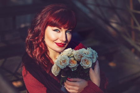 ambient light: Beautiful young woman in wool red scarf sitting on old house stairs holding flowers. Early fall. Outside shot. Ambient light. Closeup portrait. Copy space.