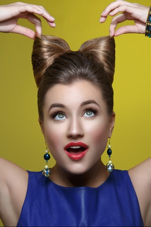 hair bow: Beautiful young woman in blue dress with makeup and hair bow style on head. Surprised expression. Studio shot over green background.