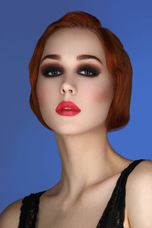 full red: Beautiful young woman with smoky eyes and full red lips. Studio beauty shot over blue background. Copy space.