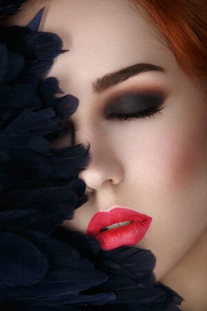 full red: Beautiful young woman with smoky eyes and full red lips. Half of face covered with blue feathers. Studio closeup beauty shot. Copy space.