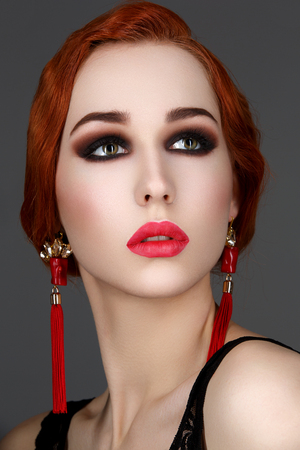 full red: Beautiful young woman with smoky eyes and full red lips. Studio beauty shot over dark background. Copy space. Stock Photo