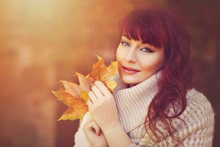 autumn colors: Beautiful young woman with red hair in wool clothes holding yellow autumn leaves. Outdoor fall shot. Sunshine. Natural background. Copy space.