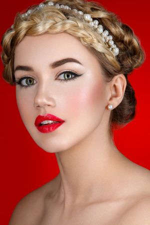 full red: Beautiful young woman with full red lips and braid hairstyle. Beauty shot over red background.