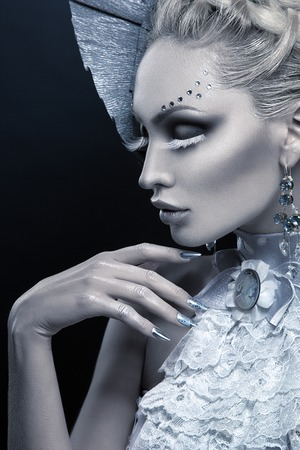 Closeup portrait of beautiful young woman dressed as winter queen. Creative makeup. Over black background. Copy space. Stock Photo - 62337805