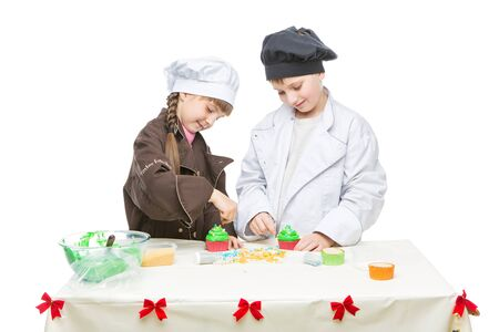 making a cupcakes beautiful boy and girl in chef clothes making christmas cupcakes children