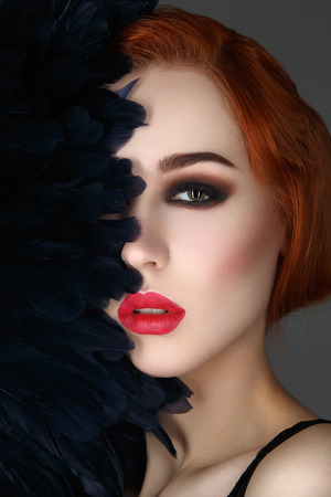 face covered: Beautiful young woman with smoky eyes and full red lips. Half of face covered with blue feathers. Studio closeup beauty shot. Copy space.