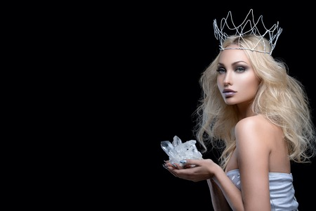 Beautiful young woman in crown holding crystal stone. Copy space.