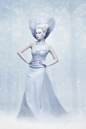 Portrait of beautiful young woman dressed as winter queen. Creative makeup. Over snow background. Copy space.