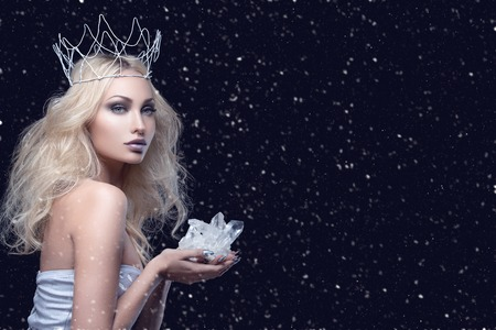 female christmas: Beautiful young woman in crown holding crystal stone. Copy space.