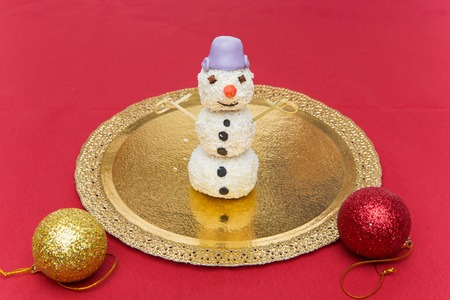 Christmas cake pop dessert in shape of snowman standing on golden folio plate. Copy space. Stock Photo