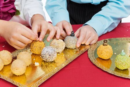 sweet pastry: Children making new year cake pop dessert in shape of christmas tree balls Stock Photo