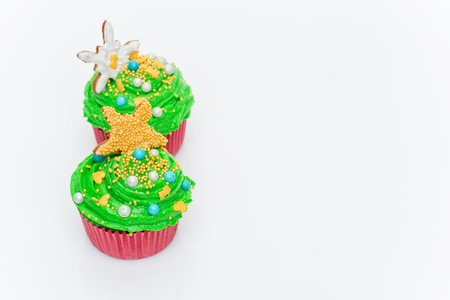 sugarpaste: Christmas tree cupcakes over white background. Copy space.